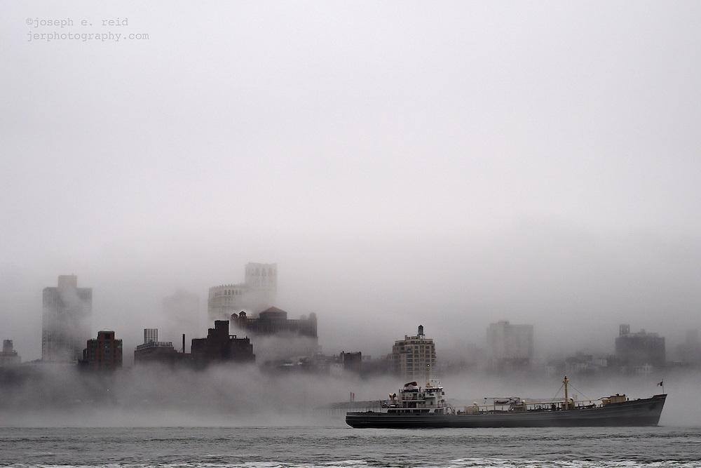 Ship passing foggy Brooklyn skyline