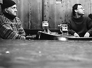 .Men sit huddled against the cold watching TV in a bar.Alcohol and bars play a big role in the neighborhood..from Neighborhoods series