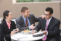 Three business people having meeting at lunch
