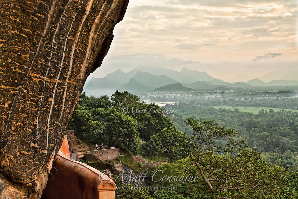 Part way up the face of the Sigiriya cliff the verdant fields and mountains of Sri Lanka open up.<br /> (Photo by Matt Considine - Images of Asia Collection)