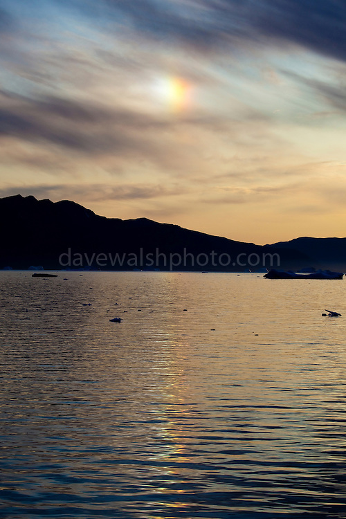 Parhelion, or sundog near Nuugaatsiaq, West Greenland. Sundogs are created by hexagonal shaped plates of ice crystals found in high and cold cirrus clouds and also in cold weather by ice crystals known as diamond dust drifting in the air at low altitudes.