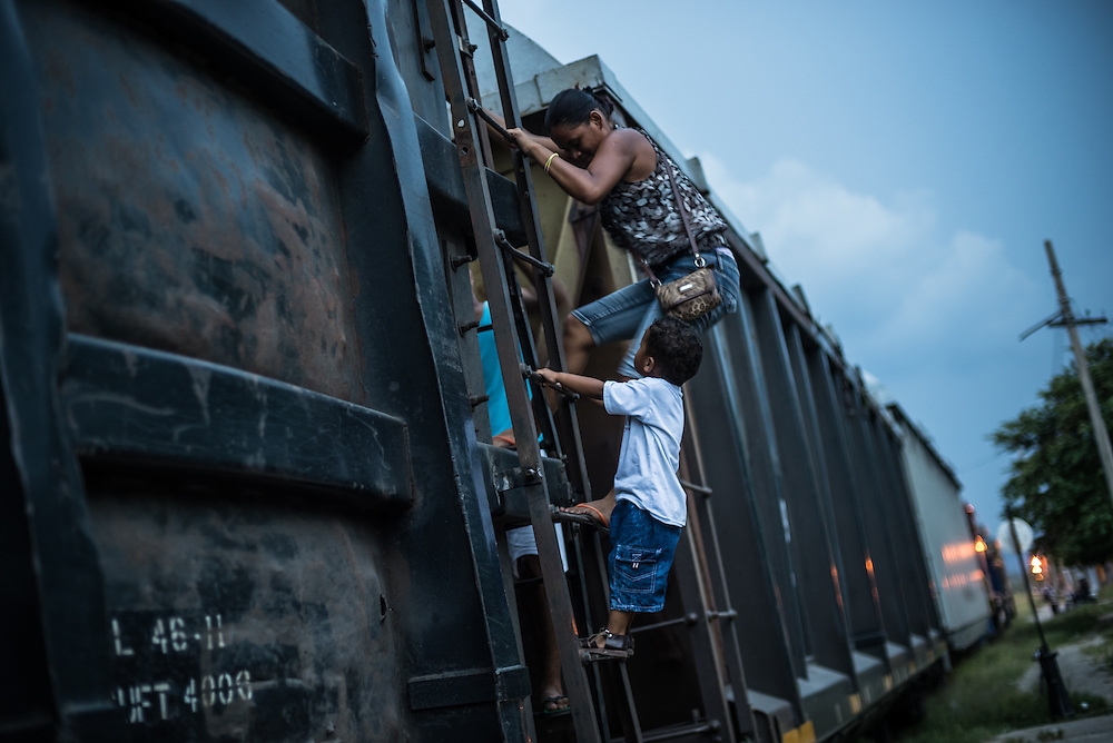 """TENOSIQUE, MEXICO - MAY 29, 2014: A migrant family climbs on top of """"The Beast"""" a train that goes from southern Mexico to just south of the Texas border, while it is parked in the train station in Tenosique, Mexico. The family was staying at the 72 migrant shelter near the train station, to rest during their travels north. The day this photo was taken, they were just practicing to see how hard it was to climb up, research for a future trip -- and got off before the train left the station. Migrants have ridden on top of its train cars for years during their journey north. PHOTO: Meridith Kohut for The New York Times"""