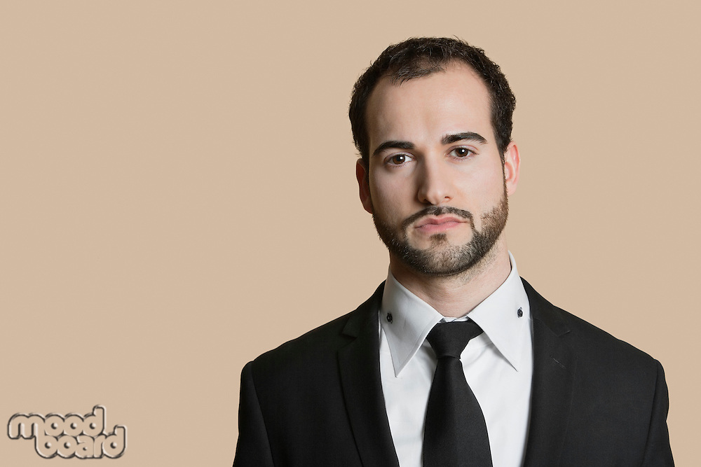 Portrait of young businessman with short hair and beard over colored background