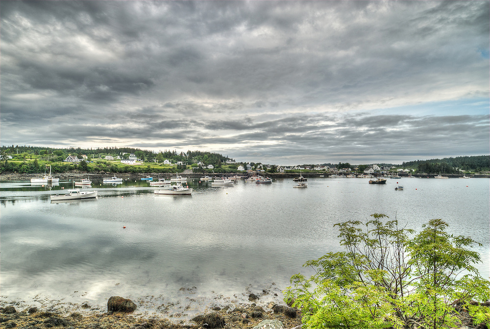 Cutler, Maine<br /> <br /> The greens of spring greeted me in Cutler, perched on one side of Little Machias Bay way up on the Maine Coast.  After a day of light to heavy rain, the sky began to break up as storm clouds moved out.  A small fleet of lobster boats were moored at low tide, the business I imagine of most of the 500 or so people in this small community.  On the docks in town, there were views of the ships and the channel to the Atlantic, stacked traps, New England architecture, and life by the sea.  But it was across the bay on a dirt road that I found my composition giving  of a sense of the fleet and it's home.