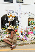 A resident prays and pay respect at a makeshift memorial outside the historic Mother Emanuel African Methodist Episcopal Church June 22, 2015 in Charleston, South Carolina. Nine people killed at the church by white supremacist, Dylann Storm Roof last Wednesday.