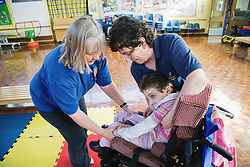 Physiotherapists positioning child in wheelchair,