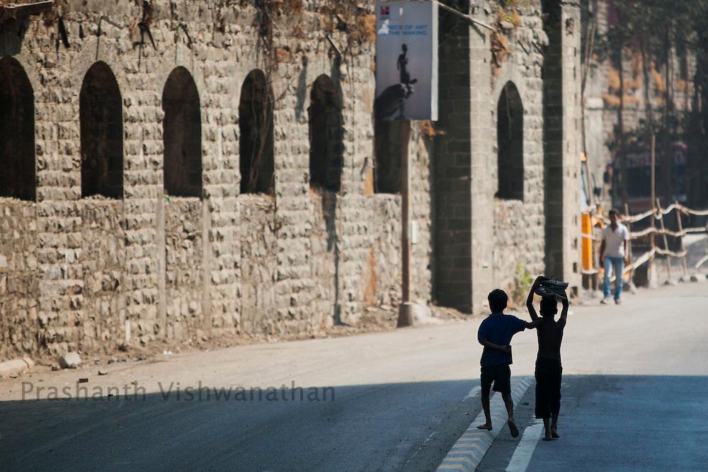 Children walk past an underconstruction, multistoried residential apartment complex in mill complex in Mumbai, Maharashtra, India, February 28, 2012. Photographer: Prashanth Vishwanathan