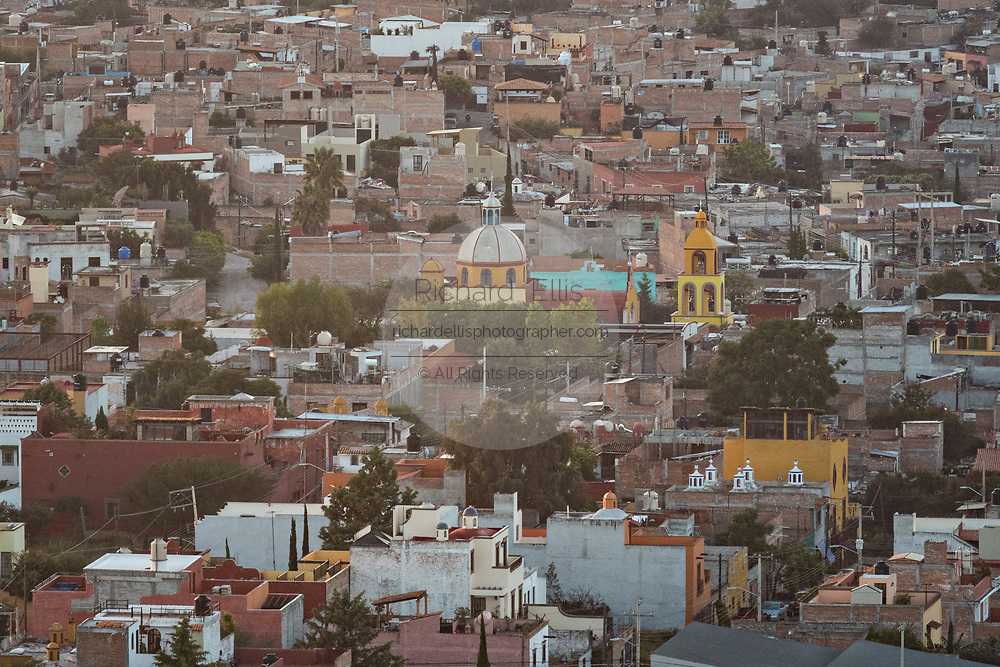 Morning fog rises over the colonial center and city landmarks in San Miguel de Allende, Mexico at dawn.
