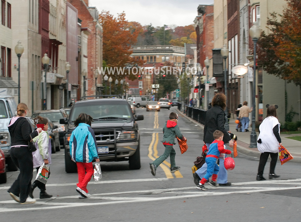 Middletown, N.Y. - Children wearing costumes and adults cross North Street on the way to getting candy from stores after a Halloween Parade on Oct. 28, 2006. ©Tom Bushey