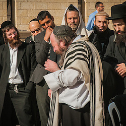 A Jewish man singing prayers in front of the Western wall while Orthodox Jews stop to listen, Jerusalem, Israel.