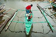 Philippines, Coron. A green bangka in a port of Coron with a little goat aboard.
