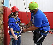 Autumn Herndon (from left), 13, of Marion, talks with Uriel Moorer, Program Specialist at Camp Courageous, at the climbing wall during the Retreat & Refresh Stroke Camp at Camp Courageous in Monticello on Saturday, April 20, 2013.