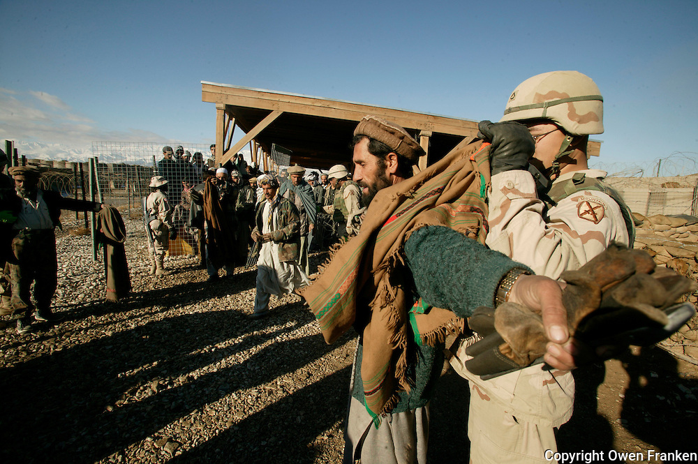 checking Afghan base workers for weapons at Baghram Army Base,Afghanistan - Photograph by Owen Franken