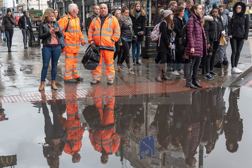© Licensed to London News Pictures. 01/11/2018. London, UK. People's reflections in a large deep rain puddle after heavy rain fall hits London at lunchtime. Photo credit: Ray Tang/LNP