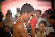 02 JULY 2006 - PHNOM PENH, CAMBODIA: A boxer thanks the crowd for their applause and tips after he won his bout during a traditional Khmer boxing match in Phnom Penh, Cambodia. Khmer boxing is the same sport as Muay Thai (traditional Thai kick boxing) but because off animosity between Thailand and Cambodia it is called Khmer Boxing in Cambodia. The Cambodians claim to have invented the sport, which is also practiced in Laos and Burma. Photo by Jack Kurtz