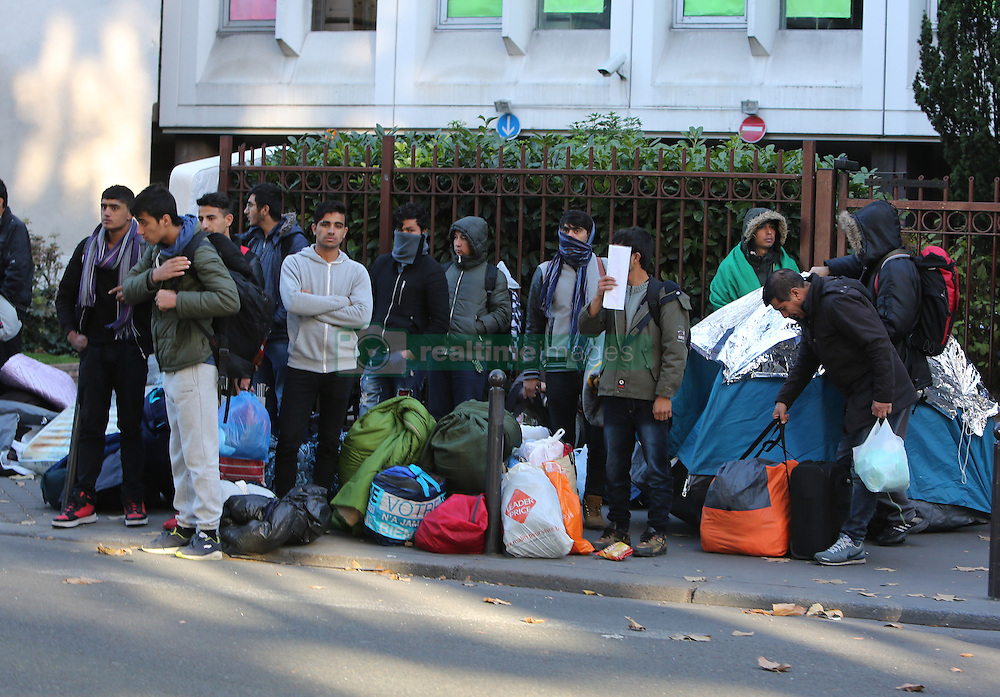 """Migrants carry their belongings at a makeshift camp at the Boulevard de la Villette, near the Jaures and Stalingrad metro stations, in northern Paris, France, on October 31, 2016, during a police operation aiming at a future evacuation of the camp. An operation of """"administrative control"""" was underway on early October 31 in the Jaures/Stalingrad quarter before a future evacuation, whose date has not yet been set, according to a police source. The makeshift camp on the outskirts of the 10th and 19th arrondissements in the north of the capital numbers today 2,500 people, according to the City of Paris. Photo by Somer/ABACAPRESS.COM"""