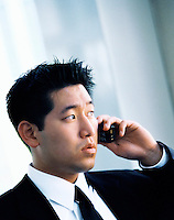 A young Asian businessman talking on a cell phone.