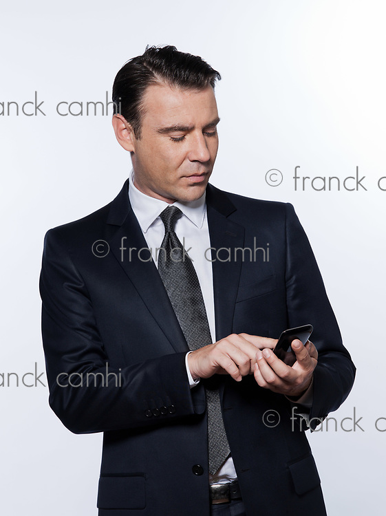 handsome caucasian man text messaging portrait isolated studio on white background wearing suit