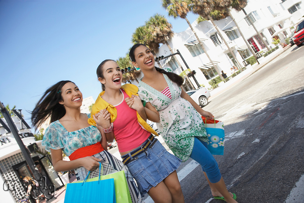 Three teenage girls (16-17) carrying shopping bags crossing street