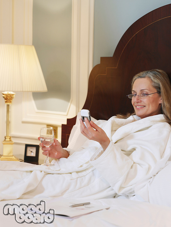 Woman wearing bathrobe using mobile phone lying on bed