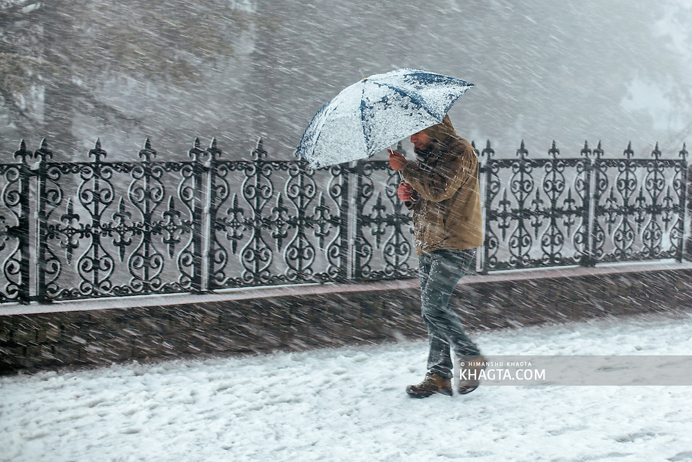 A man struggling with his umbrella during a snowstorm in Shimla, Himachal Pradesh, India