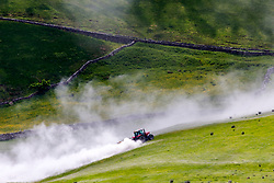 © Licensed to London News Pictures. 12/06/2018. Gearstones UK. A farmer cover's his field with Lime powder this afternoon in the sunshine bellow Ingleton mountain in the Yorkshire Dales. Farmers use lime on their fields to raise the pH level & add calcium, once the lime dissolves it releases a base that lowers the acidity of the soil improving the yield. Photo credit: Andrew McCaren/LNP