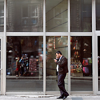 A man talks on his cell phone while walking along a street in Istanbul, Turkey