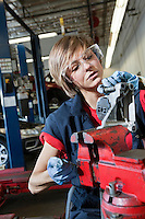 Young female mechanic in protective workwear working on machinery part in automobile repair shop