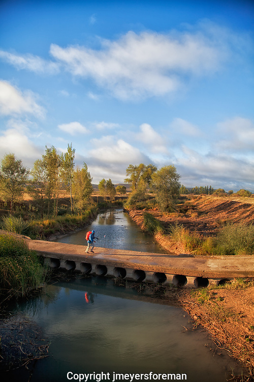 a pilgrim walkikng, all bundled against the cool morning breeze, heading west to Santiago de Compostela Spain. Crossing a cement bridge over a still stream, his red backpack reflecting in the water.