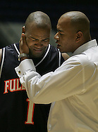 Cal State Fullerton's Jamaal Brown is comforted by assistant coach Hardy Asprilla after Long Beach State defeated the Titans 94-91 in the second round of the Big West Conference Championship at the Anaheim Convention Center Thursday March 9, 2006.