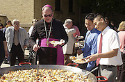 SUPER SIZE ME -- Archbishop Timothy M. Dolan scoops up a helping of paella, a Spanish seafood delicacy, during St. Lawrence Seminary's annual Family Day Sept. 26, 2004 in Mount Calvary. Archbishop Dolan was the main celebrant at the morning Mass for students, parents and alumni, and special guest at the all-school family picnic that followed. The picnic includes multi-ethnic dishes, featuring paella, a traditional seafood dish that includes shrimp, grouper, mussels, calamari, vegetables and rice. Pictured with Archbishop Dolan are St. Lawrence alumni Songkanh Vongphouthone, center, and Son Nguyen. (Catholic Herald photo by Sam Lucero)