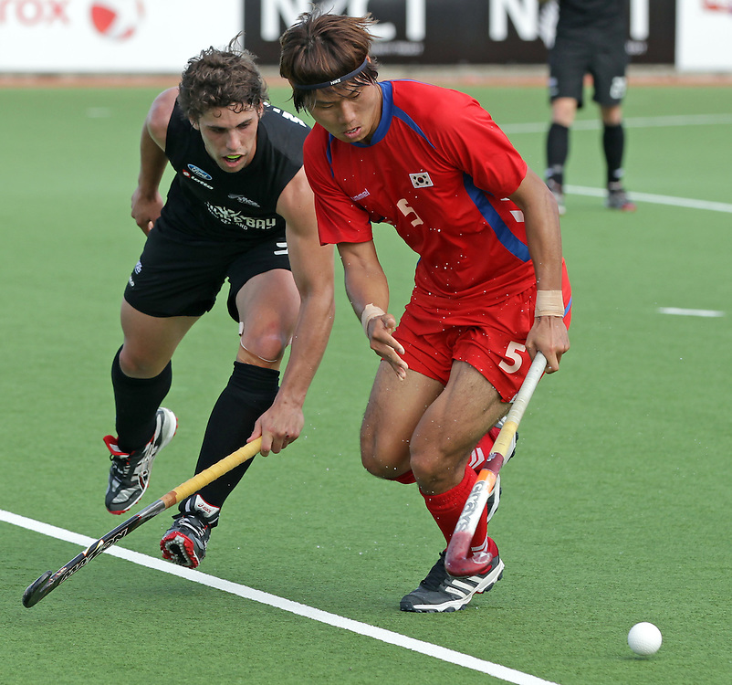 New Zealand's Nick Wilson challenges Korea's Hyun Woo Nam in a pool B match of the Hockey Champions Trophy, Auckland, New Zealand, Monday, December 05, 2011.  Credit:SNPA / David Rowland
