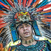 Head and shoulders of Aztec dancers in his regalia at Drums Along the Hudson, in Inwood Hill Park, NYC.<br /> <br />  Every movement in the choreography of dance has a specific meaning. Squats and serpentine movements represent fertility, steps firmly on the ground and planting land, air and turns the spirit, advanced steps and retroceded fire and water zigzagging steps. Always relation to the four elements is found. water, fire, wind, earth.<br /> <br /> Also this number is prevalent in Mexican culture as it also represents the four directions, north, south, east, west among other interpretations. Azteca dance origins / Mexihca in