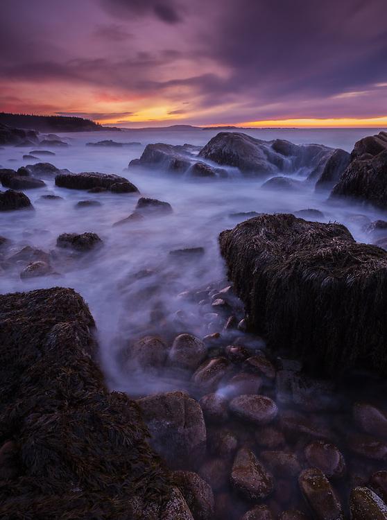 Dramatic sunrise light along the rocky coast of Acadia National Park in Maine.