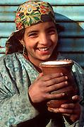 INDIA, PORTRAITS Portrait of young girl with a pot of yogurt in Srinagar, Kashmir