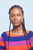Portrait of serious young woman with braided hair against light blue background