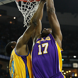 February 5, 2011; New Orleans, LA, USA; Los Angeles Lakers center Andrew Bynum (17) dunks over New Orleans Hornets center D.J. Mbenga (28) during the first quarter at the New Orleans Arena.   Mandatory Credit: Derick E. Hingle