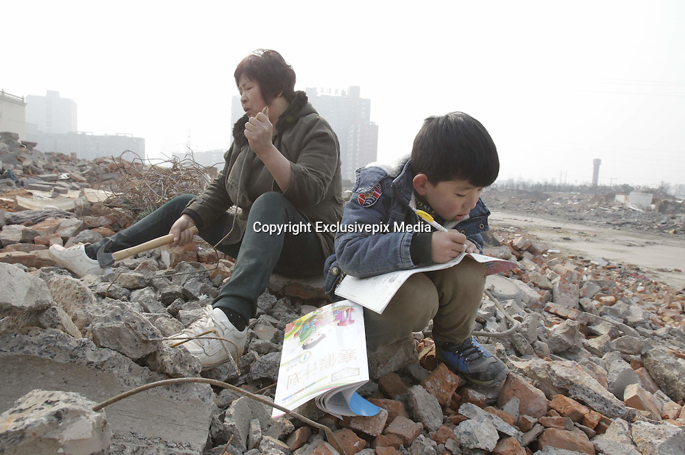 ZHENGZHOU, CHINA - FEBRUARY 03: (CHINA OUT) <br /> <br /> 7-year Old Child Picks Up Used Wires For Sick Father<br /> <br /> Seven years old Lele writes homework when his grandmother picking up used wires near west 3rd Ring Road and Huagong Road on February 3, 2015 in Zhengzhou, Henan province of China. A seven years old child who was in first grade picked up wasted wires with his grandmother Liu Xiaohong to make money for his sick father who had got Hepatitis-Aplastic Anemia Syndrome. They had almost run out all savings but failing in curing his father. Lele\'s mother looked after his father and he and grandmother had to do something else to support the family. Their efforts in all day would only be paid back forty or fifty Yuan RMB (6 USD - 8USD) and even though Lele still wrote his homework when resting along with his grandmother. Lele said that he would be a doctor to save father. <br /> &copy;Exclusivepix Media