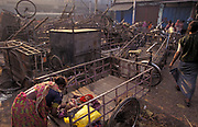 Among a pile of market carts, a mother bends over to attend to her young child at a street market, on 18th November 1996, in Kolkata, India.