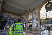 Police officers keep watch beneath traditional Azulejo tiles inside the ornate Sao Bento railway station in Porto, Portugal.