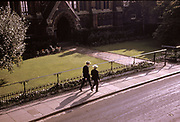 Two school boys in hats walking down the street past a church, Harrow School, Middlesex, UK, 1962
