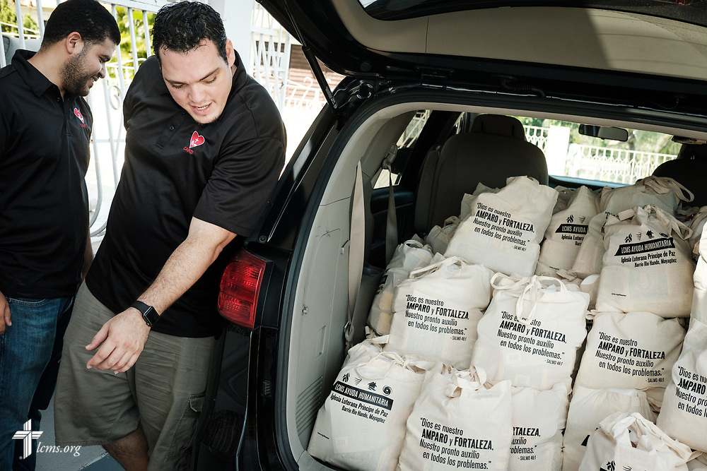 Evangelist William Torres and the Rev. Gustavo Maita, pastor of Iglesia Luterana Principe de Paz (Prince of Peace Lutheran Church), Mayagüez, Puerto Rico, finish loading bags of food and supplies at the Casa de Amparo y Respuesta a Desastre (CARD), or House of Refuge and Mercy Response mercy center, on Tuesday, April 17, 2018 in Mayagüez. LCMS Communications/Erik M. Lunsford