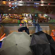 Two women huddle together under umbrellas to get some privacy on a fly-over in Hong Kong Central on a Sunday evening. Hong Kong has a huge Filipino population, most of them women working as domestic servants. They meet in public on their days off since none of them have their own private accomodation.7 million people live on 1,104km square, making it Hong Kong the most vertical city in the world.