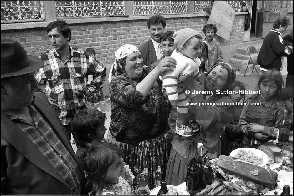 GEORGIANA OLGA GREANCIU IS HELD IN THE AIR AFTER RECEIVING HER FIRST GOLD COIN. ROMANIAN ORTHODOX EASTER CELEBRATIONS. SINTESTI, ROMANIA. MAY 1997..©JEREMY SUTTON-HIBBERT 2000..TEL./FAX.+44-141-649-2912..TEL.  +44-7831-138817.