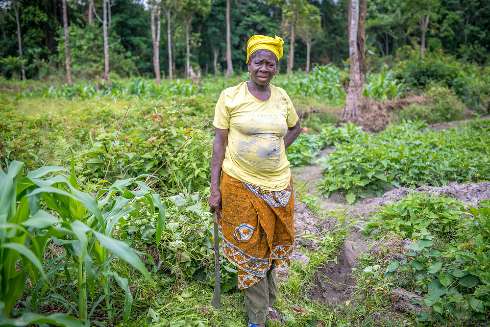 A woman poses for the camera amongst produce on a farm in Ganta, Liberia