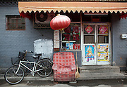 An empty chair in front of a kiosk in a Beijing hutong.