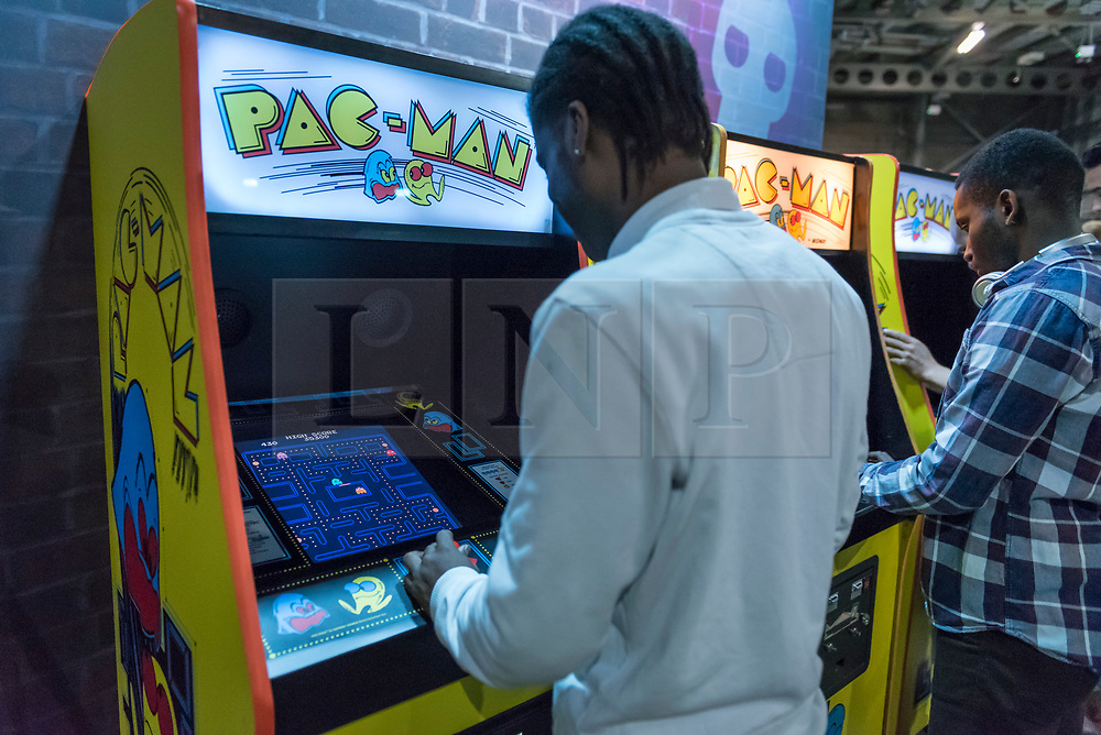 © Licensed to London News Pictures. 12/08/2018. LONDON, UK. People play Pac-Man at Play Expo London, a video games show featuring consoles, handhelds, computers, vintage arcades and pinball machines, organised by Replay Events taking place at the Printworks in Canada Water, East London.  Photo credit: Stephen Chung/LNP