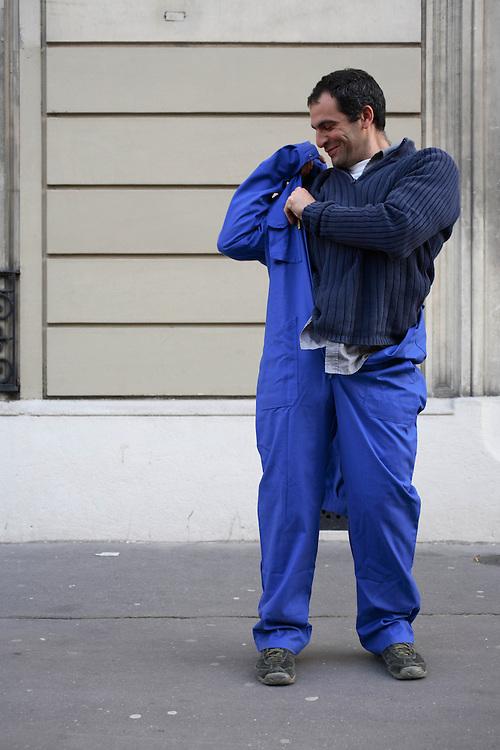 """BLEUS de TRAVAIL : J'ai demande a des inconnus dans la rue d'enfiler un BLEU DE TRAVAIL. La plupart n'en avait jamais porte. Si ce vetement prend tout le corps, il ne s'agissait pas pour autant d'endosser la FONCTION et de jouer a l'ouvrier, mais plutot de se preter a un exercice CHOREGRAPHIQUE. Place du bresil, paris 17e /  GUSTAVO, photographe : """"c'est PAS premiere fois""""."""