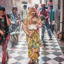 Women soaked in coloured water during the celebrations of holi festival, Vrindavan, India