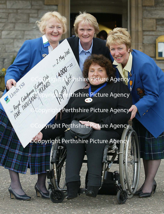 Curling meeting Pitlochry...14.5.2001.<br />Disabled curler Elaine Lister of Glenrothes receiving a cheque from Royal Caledonian Curling Club Ladies President Kathleen Scott, left, World Curling Federation representative Kate Caithness,right, and Scottish Gold medal winning skip Rhona Martin.<br /><br />Picture by John Lindsay .<br />COPYRIGHT: Perthshire Picture Agency.<br />Tel. 01738 623350 / 07775 852112.